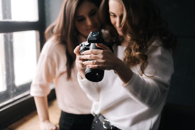 Модель и женщина-фотограф, глядя на сделанное фото и улыбаясь в студии