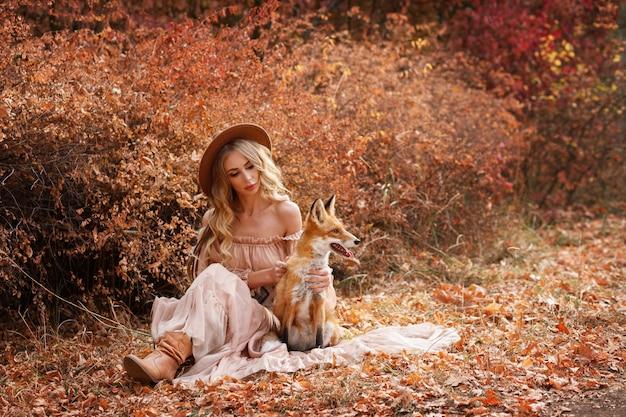 Модель и рыжая лиса на красном фоне лиственных