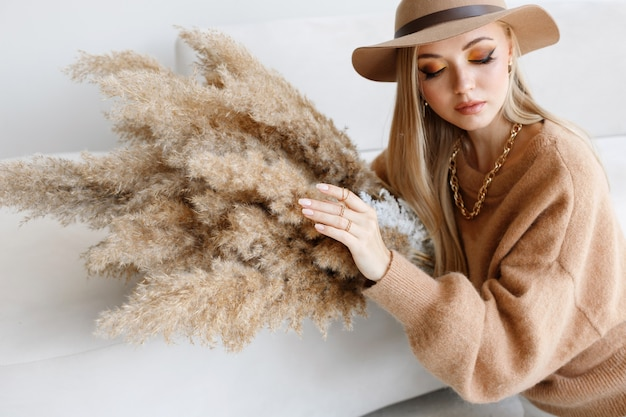 Model in autumn clothes with dry flowers, makeup and manicure. close-up