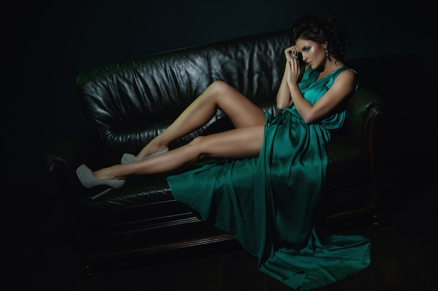 Model in beautiful green dress posing on leather couch