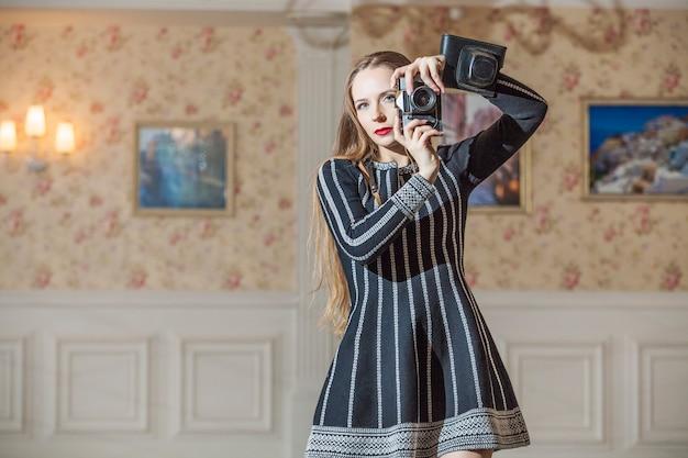 高級ヴィンテージレトロインテリアの中でファッショナブルな服を着た美しい女性をモデル化する