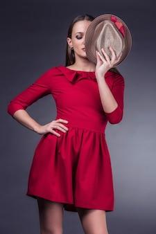 黒の背景で隔離のファッショナブルな服やアクセサリーのショットで美しい女性をモデル化する