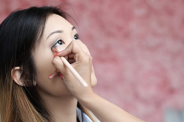 Model being makeup by professionals