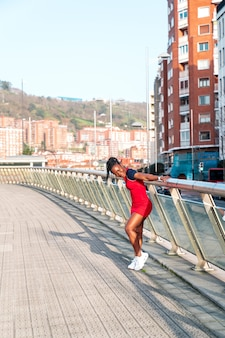 Model black afro girl posing smiling and fun in the city at sunset wearing a red dress and white sneakers