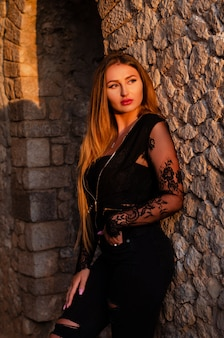 Model in black clothes posing outdoors nex to the ancient wall on natural sunset light.