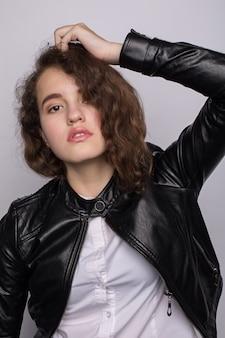 Model in a black jacket on a white background, fashion portrait.