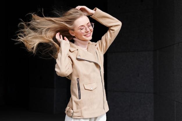 산책을 위해 강한 바람에 긴 머리를 가진 모델 금발