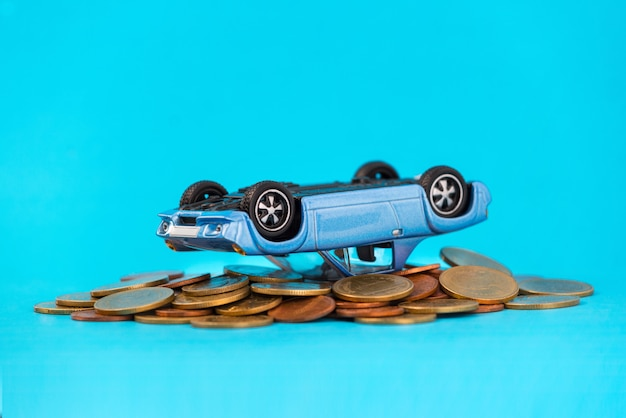 Model blue car overturned composition on stack golden coins