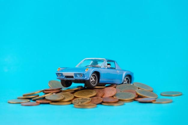 Model blue car park on stack golden coins
