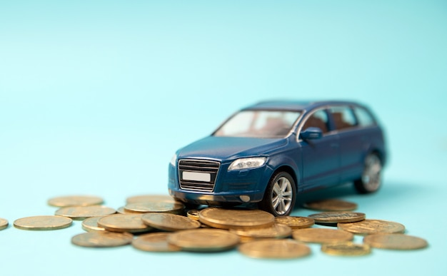 Model blue toy suv car parking on coins