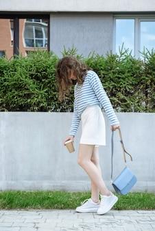 새 옷 카탈로그에서 거리의 배경에 포즈를 취한 커피와 가방을 가진 모델 갈색 머리 여자