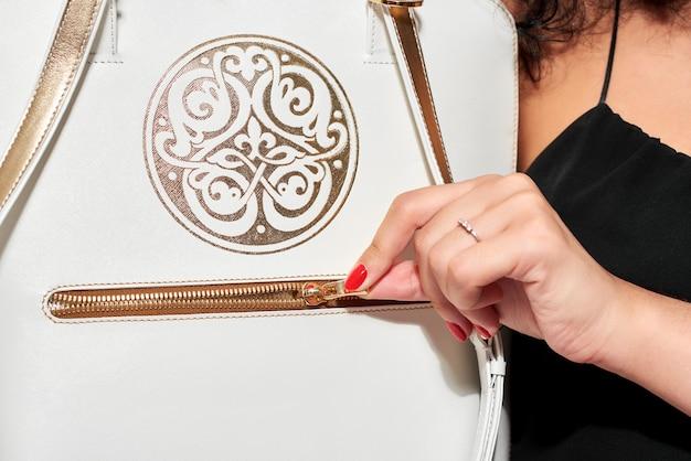 Модель-переноска белая сумка с золотым узором, ручками и маленькой молнией.