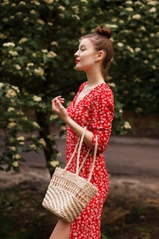 Model in a city park holds a straw bag. stylish summer wear. flowering trees in the background