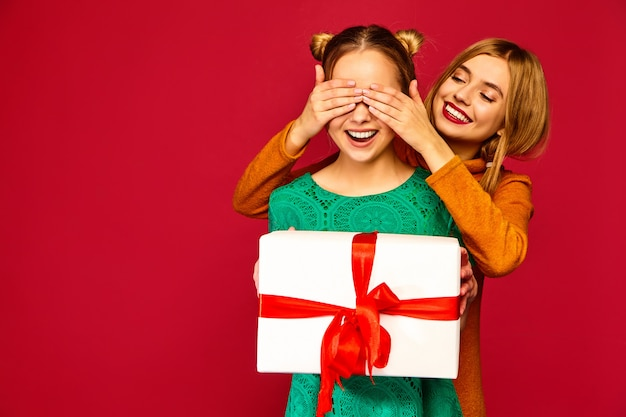 Model covering eyes her friend and giving her big gift box