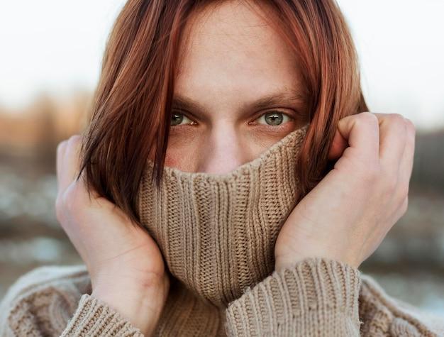 Modello che copre il viso con un maglione beige