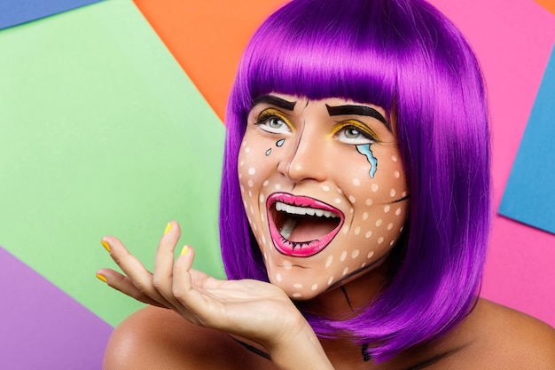 Model in creative image with pop art makeup against colorful