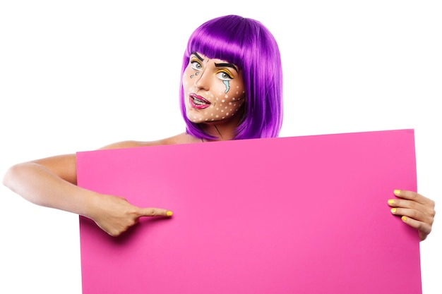 Model in creative image with pop art makeup is holding pink blank board isolated on white