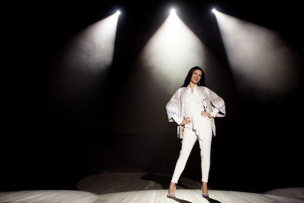 모델은 하얀 빛, 어두운 배경, 연기, 콘서트 스포트라이트 광선의 무대에서 옷을 보여줍니다.