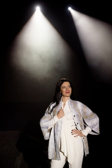 Model demonstrates clothes on the stage in the rays of white light, dark background, smoke, concert spotlights.