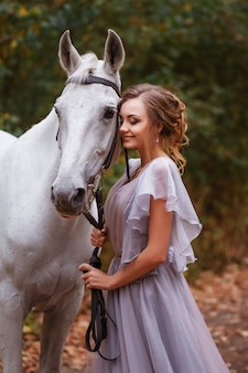 Model in a dress smiles and holds a white horse. background blurred, artistic effect. green leafy background