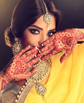 伝統的な国民のスーツのサリーに身を包んだモデルは、彼女の手のひらに一時的な刺青ヘナのタトゥーと伝統的なクンダンスタイルのジュエリーセットを示しています美しい黒い目の遊び心のある外観