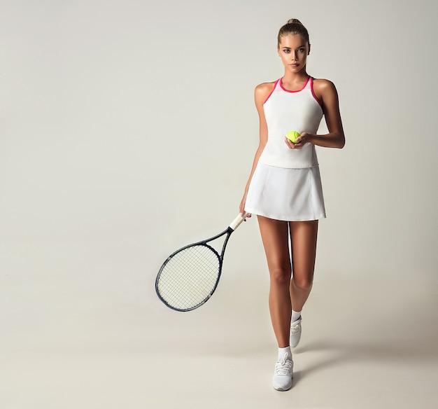 白いスポーツ服を着たモデルは、テニスラケットとボールを手に持って前進します。ダイナミックな動き。スポーツと美しさ。