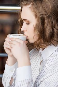 모델 음료 카푸치노 커피. 클로즈 업 초상화. 배경 흐리게 개념