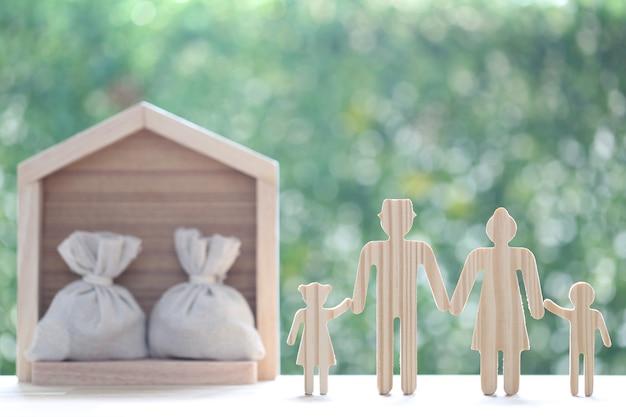 自然な緑の背景にモデル家族とモデルハウス