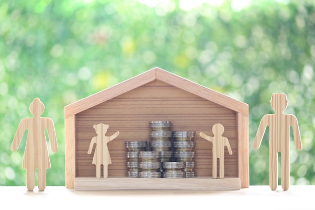 Model family and stack of coins money in model house on natural green background
