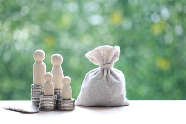 Model family on stack of coins money with money bag on natural green background,save money for prepare in future and family finance concept