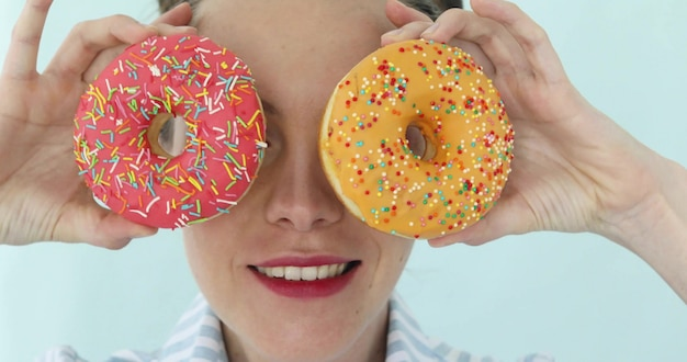 Model girl holding colorful pink donuts against her eyes.