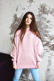 Модель девушка в розовой пустой толстовке с капюшоном и синих джинсах, глядя в камеру, позируя в помещении. молодая женщина в повседневной одежде