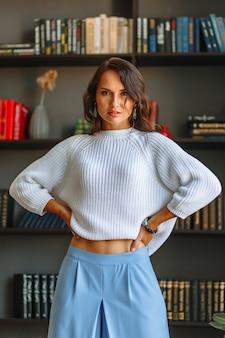 本棚を背景に、白いブラウスと青いパンツのモデルの女の子