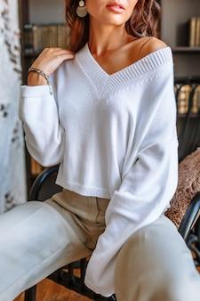 椅子に座っている白いジャケットのモデルの女の子