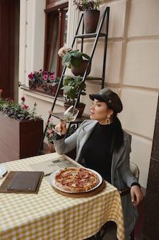 Модель девушки в модной одежде сидит на открытом воздухе за столиком в кафе, пьет вино и ест пиццу