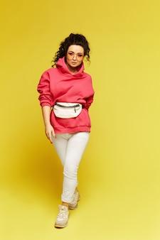 ピンクのジャージ、モダンなサングラス、黄色に分離されたベルトバッグのモデルの女の子