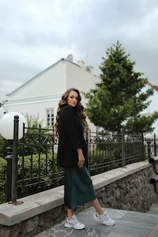 夏の日に旧ヨーロッパの街の通りでポーズをとるスタイリッシュなドレスとスニーカーのモデルの女の子