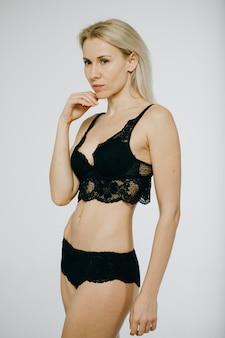 スタジオでポーズをとるモデルの女の子。黒いパンティー、黒いブラジャー、セクシーなランジェリーとうれしそうなファッション女性