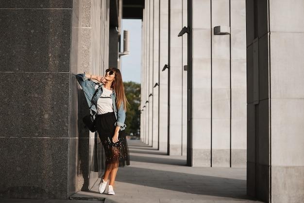 도시 거리에서 혼자 포즈를 취하는 검은 치마, 데님 해켓 및 선글라스를 착용 한 모델 소녀