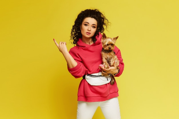 分離された黄色の背景に小さなかわいい犬と一緒にポーズをとるスポーツウェアを着たアフロの髪のモデルの女の子