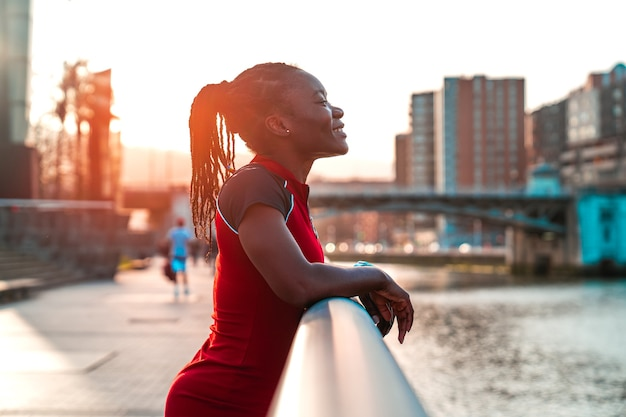 Model girl with black skin and afro style hair posing smiling holding on to the railing of a bridge by the river of a city in a beautiful sunset with warm colours in a red dress
