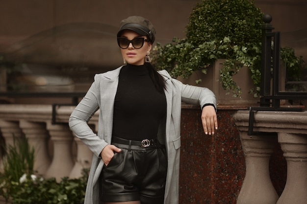 Model girl with full sexy lips wearing trench-coat, sunglasses, and shorts posing outdoors on the autumn day
