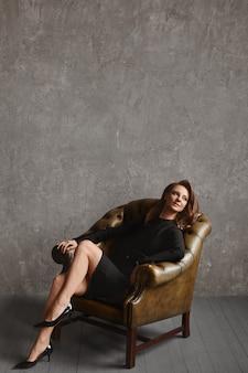빈 아파트에서 빈티지 가죽 안락의 자에 앉아 유행 드레스에 긴 다리를 가진 모델 소녀