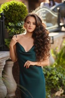 夏の晴れた日に屋外でポーズをとる流行の夏のドレスで完璧なメイクのモデルの女の子