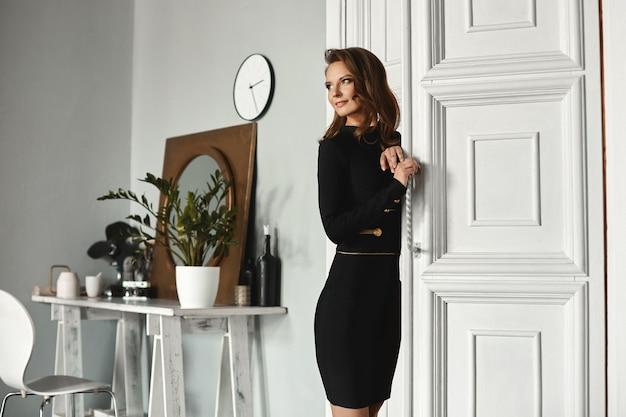 화이트 인테리어의 빈티지 문 근처에서 포즈를 취하는 칵테일 블랙 드레스에 완벽한 슬림 바디와 모델 소녀
