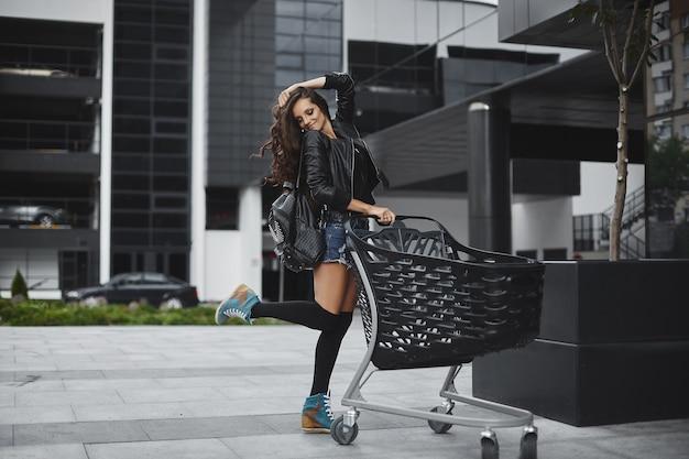 반바지, 스타킹 및 가죽 재킷에 완벽한 슬림 바디를 가진 모델 소녀가 매장 근처의 거리에서 쇼핑 카트와 함께 포즈를 취합니다.