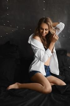 デニムのショートパンツとボタンを外したシャツを着た完璧なスポーティなボディのモデルの女の子が朝のベッドでポーズをとる