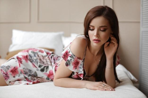 短い夏のドレスでスリムなボディを持つモデルの女の子はベッドで休む