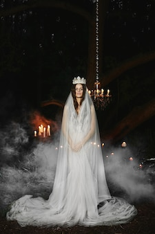 Model girl with in white lingerie with a crown and a veil on her head stands in a foggy forest, fairytale picture