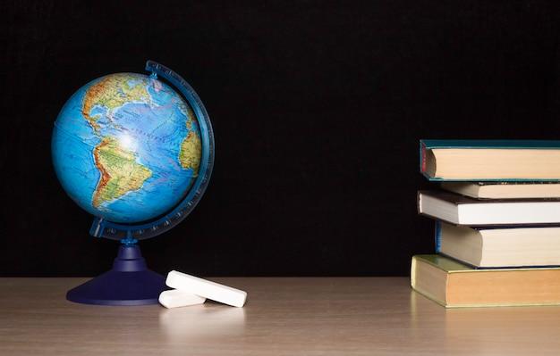 テーブルの上の地球儀、チョーク、暗い背景の本のスタックをモデル化します。学校、トレーニング、知識を得るという概念